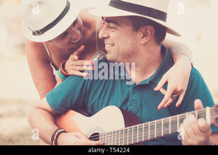 Romantic hug an colors with cheerful happy middle age people in love playing a guitar together looking and smiling - relationship for middle age adult - Stock Photo
