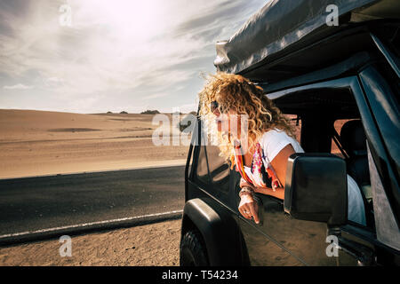 Beautiful lady caucasian people female enjoy th ewind in the outdoor nature out of her black car - desert outdoor around and alternative vacation jour - Stock Photo