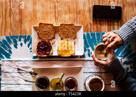 Vertical top point of view of woman doing breakfast in hotel or home - bread and mermalades and coffee time for healthy energy food to start the day - - Stock Photo