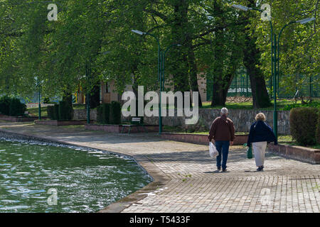Two older people strolling along the shore of the lake on a cool spring day. - Stock Photo