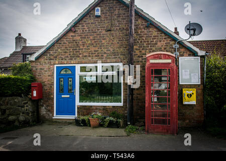 Old and new. You can see the old phone booth and post box against the new defibrillator and modern shop in a yorkshire village, uk. - Stock Photo