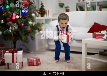 A boy with a New Year's gift. Emotions from receiving a Christmas gift - Stock Photo