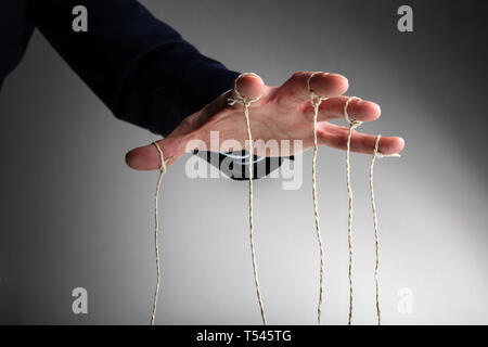 Close-up Of Person's Hand Controlling Puppet Against Gray Background - Stock Photo