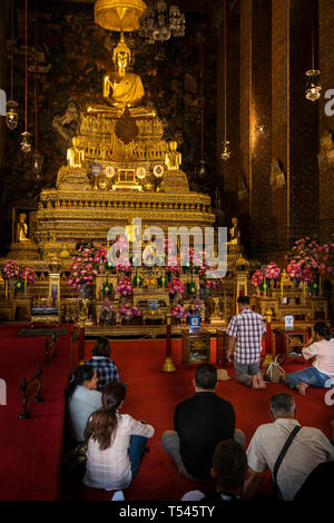 Thailand, Bangkok, Wat Pho, Phra Ubosot, worshippers praying in the ordination hall - Stock Photo