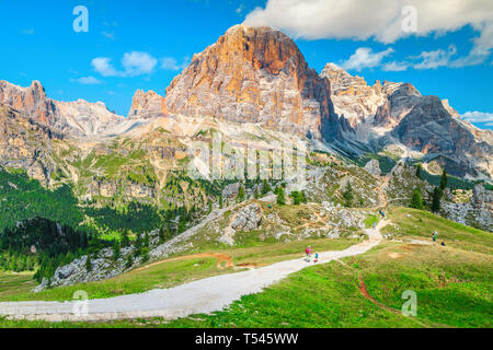 Sporty healthy active group of hikers with colorful backpacks walking on the mountain trail,near Cortina d Ampezzo, Dolomites, Italy, Europe - Stock Photo