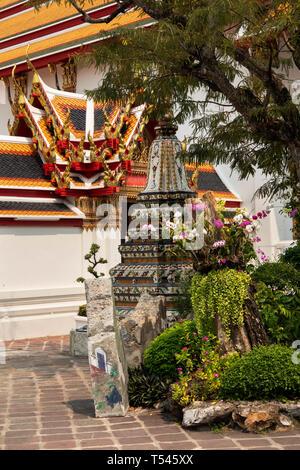 Thailand, Bangkok, Wat Pho, Phra Maha Chedi, orchids growing next to small memorial Chedi - Stock Photo