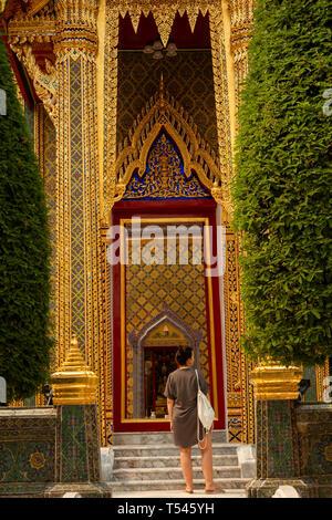 Thailand, Bangkok, Thanon Fuang Nakhon, Wat Ratchabophit Sathitmahasimaram, woman at main entrance - Stock Photo