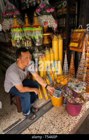 Thailand, Bangkok, Thanon Bamrung Mueang, Buddhist Supplies Shop, vendor showing price of large temple candles on calculator - Stock Photo