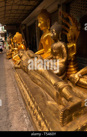 Thailand, Bangkok, Thanon Bamrung Mueang, Soi Mahannop2, Buddhist Supplies Shop, large golden reclining and seated buddhas for sale - Stock Photo