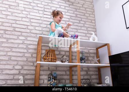 Low Angle View Of Smiling Girl Sitting On Shelf In Home