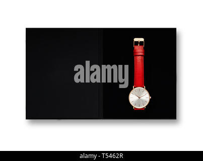 Classic women's gold watch with white dial, red leather strap, isolate on a white background. View from the top in the box. - Stock Photo
