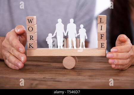 Couple Protecting Work And Life Balance With Family Figures Standing Between Them On Seesaw - Stock Photo