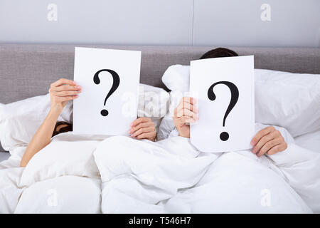 Couple Lying On Bed Holding Question Mark Sign In Front Of Their Face - Stock Photo