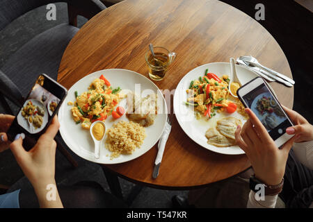 Women blogger takes photos of her food in a cafe using mobile phone. Hands with phone screen close-up. - Stock Photo