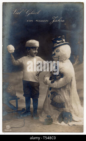 Boy and snowman depicted in the vintage Austrian New Year postcard issued before 1912. Text in German means: Good luck in the New Years (Viel Glück im Neuen Jahre). Courtesy of the Azoor Postcard Collection. - Stock Photo