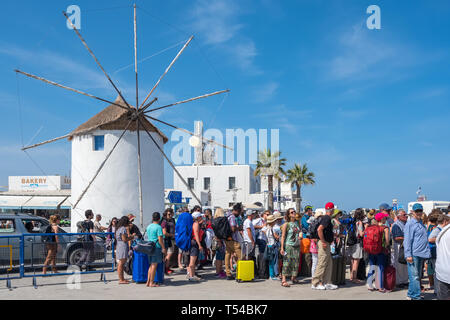 Paros, Greece - June 5, 2018: Unidentified tourists waiting in line to ferry boat with a Traditional cycladic windmill at background on Paros island,  - Stock Photo