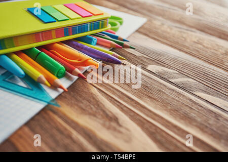 Education concept. Pens, pencils, markers, ruler and brush on notebook. on a wooden background. flat lay - Stock Photo