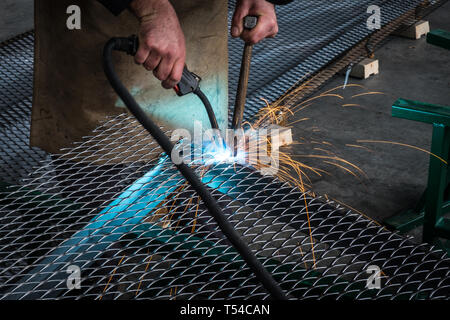 Worker welding steel mesh to the frame with MIG technology - Stock Photo