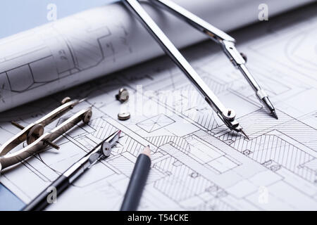Compass on the details of the industrial drawing. architectural background with rolls of technical drawings and blueprints. selective focus - Stock Photo