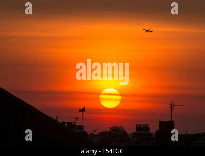 London, UK. 20th April, 2019. Aircraft takes off from Heathrow as the sun sets over suburban rooftops in a clear orange sky after a day of cloudless skies and soaring summer temperatures during Easter holiday weekend. Credit: Malcolm Park/Alamy Live News. - Stock Photo