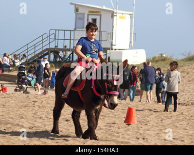Skegness, UK. 20th Apr, 2019. Child seen riding a donkey on the beach at Skegness during Easter.People enjoy the unseasonably warm Easter weather in the UK - especially the children having donkey rides on the sandy beach at Skegness. The traditional seaside attraction started in Victorian times, but is now seen much less in the major resorts, but is still popular on the Lincolnshire beaches of Skegness, Mablethorpe and Ingoldmells. Credit: Keith Mayhew/SOPA Images/ZUMA Wire/Alamy Live News - Stock Photo