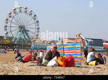 Skegness, UK. 20th Apr, 2019. A tourist seen next to a wind break during Easter. People enjoy the unseasonably warm Easter weather in the UK - especially the children having donkey rides on the sandy beach at Skegness. The traditional seaside attraction started in Victorian times, but is now seen much less in the major resorts, but is still popular on the Lincolnshire beaches of Skegness, Mablethorpe and Ingoldmells. Credit: SOPA Images Limited/Alamy Live News - Stock Photo