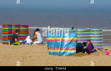 Skegness, UK. 20th Apr, 2019. Wind breaks seen used by tourists during Easter. People enjoy the unseasonably warm Easter weather in the UK - especially the children having donkey rides on the sandy beach at Skegness. The traditional seaside attraction started in Victorian times, but is now seen much less in the major resorts, but is still popular on the Lincolnshire beaches of Skegness, Mablethorpe and Ingoldmells. Credit: SOPA Images Limited/Alamy Live News - Stock Photo