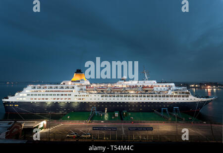 Cobh, Cork, Ireland. 20th April, 2019. Cruise liner Saga Sapphire docked at the deep water berth at dusk during her overnight stay in Cobh, Co. Cork, Ireland. Credit: David Creedon/Alamy Live News - Stock Photo