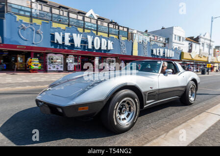Classic car show taking place along the seafront at Marine Parade, Southend on Sea, Essex, UK. Chevrolet Corvette Stingray driving past New York amusement arcade - Stock Photo