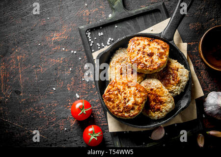 Cutlets in the pan on the paper with garlic and tomatoes. On dark rustic background