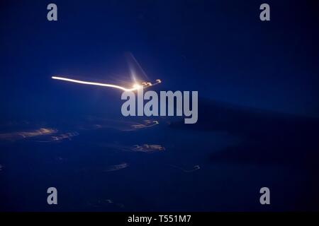 Airplane wing light in motion from the airplane window at night. - Stock Photo