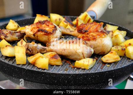 Roast chicken and potatoes on cast iron platter - Stock Photo