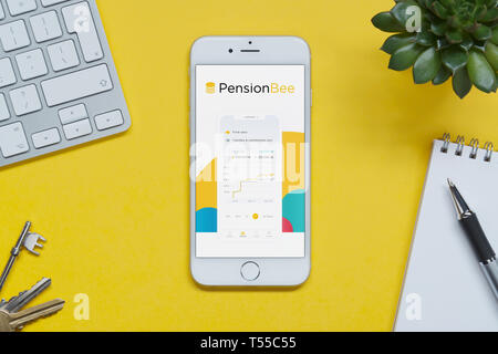 An iPhone showing the Pension Bee website rests on a yellow background table with a keyboard, keys, notepad and plant (Editorial use only). - Stock Photo