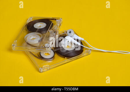 Retro technology. Plastic transparent audio cassette and white vacuum headphones on a bright yellow background. 80s. - Stock Photo
