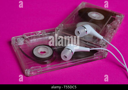 Retro technology. Plastic transparent audio cassette and white vacuum headphones on a bright pink background. 80s. - Stock Photo