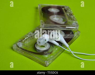 Retro technology. Plastic transparent audio cassette and white vacuum headphones on a bright green background. 80s. - Stock Photo