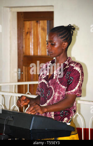 Young woman playing musical instrument in the Baptist church, Arusha - Tanzania - Stock Photo