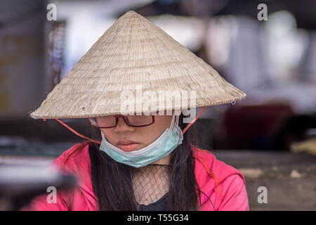 Portrait o a young Vietnamese woman wearing traditional conical hat