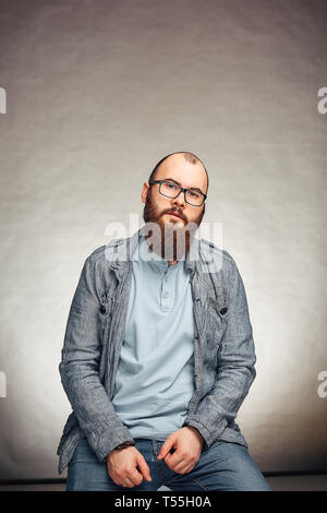 lifestyle successful young man with glasses , beard, fashionable denim jacket looking forward,male portrait in the Studio on a uniform background. - Stock Photo