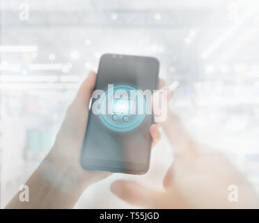 Shopping basket on a mobile phone screen. Woman Hand holding mobile phone on Supermarket blur background - Stock Photo