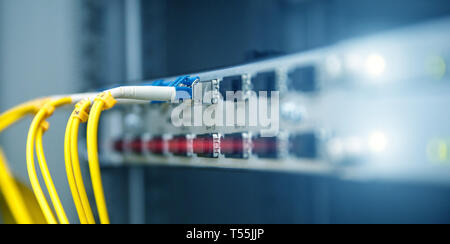 Technology banner. Close up fiber optic cable. Servers racks. Severs computer in a rack at the large data center. Photo contains noise - Stock Photo