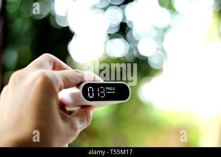 measuring outdoors air quality. A hand holding particulate matter 2.5 (pm.2.5) sensor. harmful small dust detector indicated healthy acceptable air qu