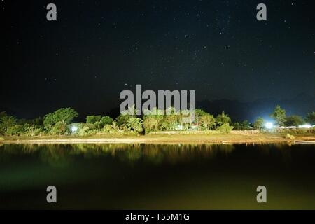 star lit sky. sky fill of stars over serene small river in Vangviag province, Laos. forest riparian river bank in the night. peaceful scene of a raw v - Stock Photo