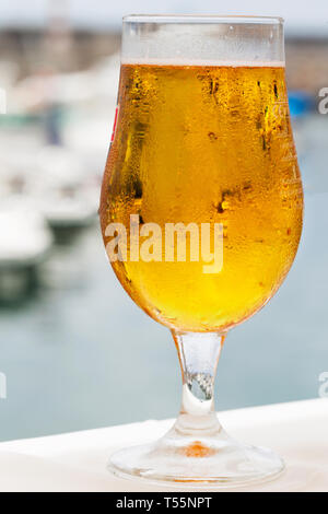 A sweaty glass of cold beer on the background of the marina and yachts in the port. Close-up of water droplets on a glass with a yellow drink - Stock Photo