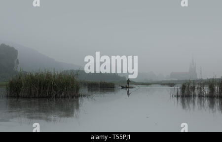 Fisherman on wood boat hunting with long stick on a foggy morning with church in background, Van Long Wetland Nature Reserve, Ninh Binh, Vietnam, Asia - Stock Photo