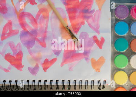 Paintbrush on watercolor painting of hearts by paints - Stock Photo