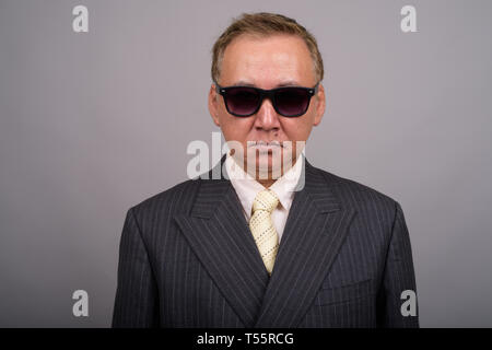 Portrait of mature Asian businessman against gray background - Stock Photo