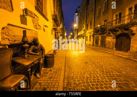 Sculpture of man sitting at table at night in Lviv, Ukraine - Stock Photo