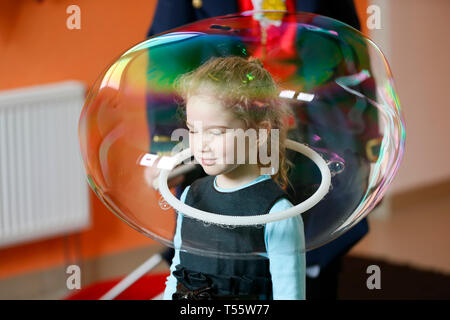Belarus, the city of Gomel on April 10, 2016, the central children's store.Show of soap bubbles.Little girl inside the soap bubble - Stock Photo