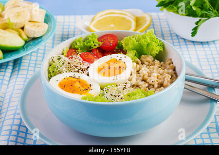 Fresh salad. Breakfast bowl with oatmeal, tomatoes, lettuce, microgreens and boiled egg. Healthy food. Vegetarian buddha bowl. - Stock Photo